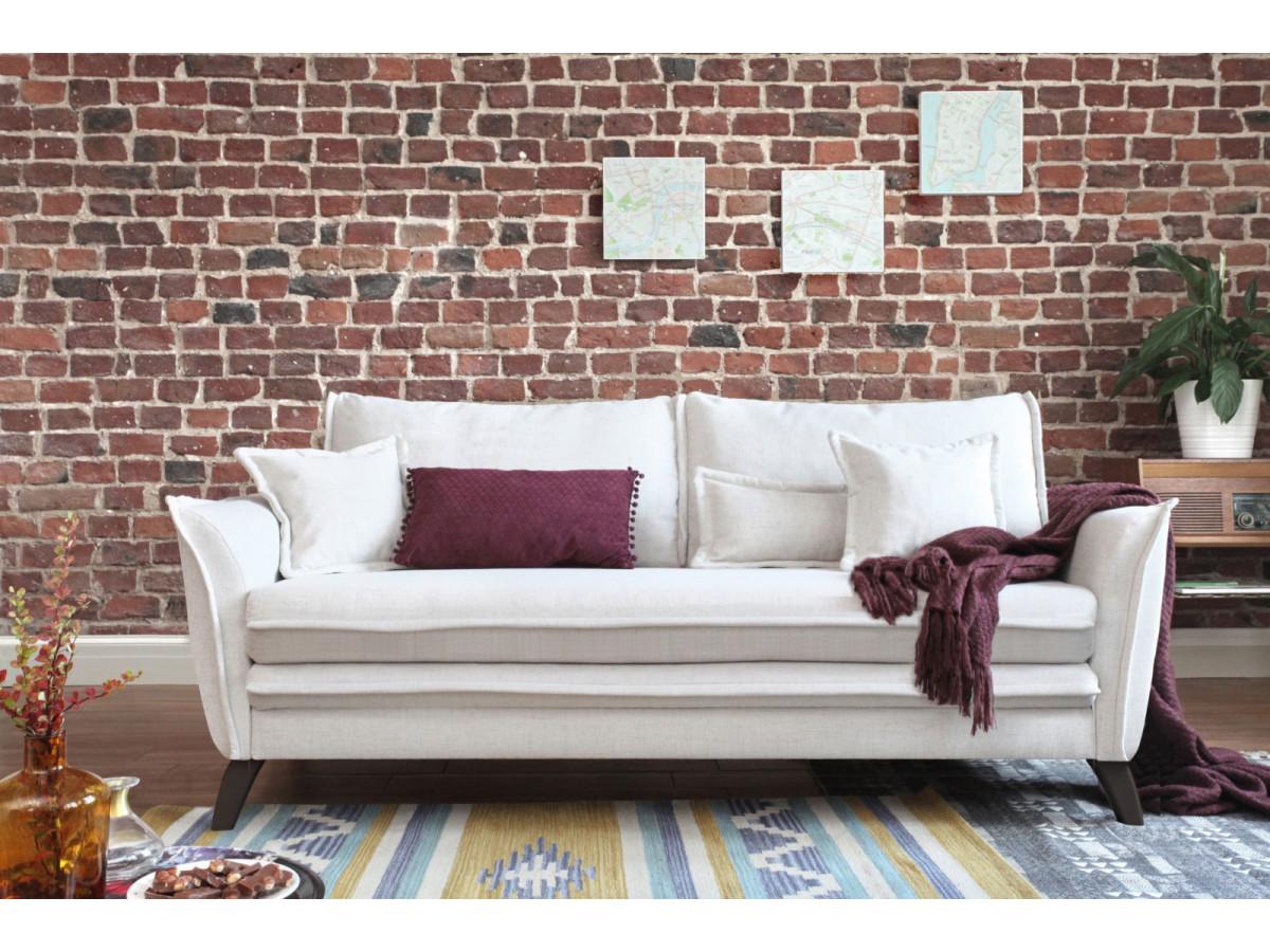 salon mur brique accessoiriser canapé lin blanc coussin prune plaid tricot